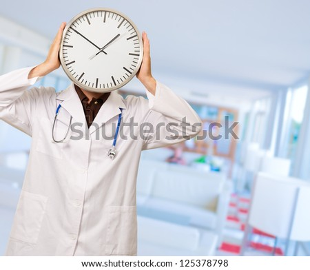 Portrait Of Doctor Hiding Face With Clock, Indoors