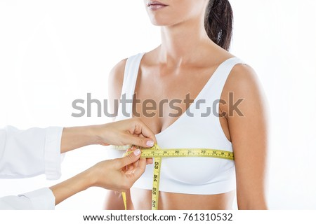 Portrait of doctor with measure tape measuring the size of the patient's breast.