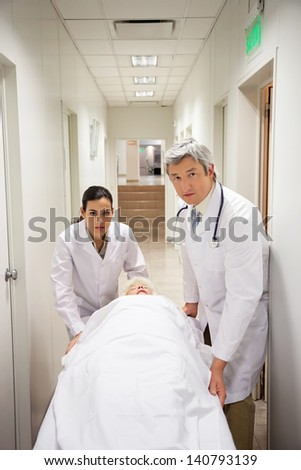 Portrait of doctors with patient in hospital corridor