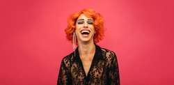 Portrait of drag queen laughing on red background. Gender fluid male dressed as female laughing.