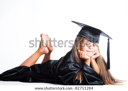 Portrait of dreaming cute girl in black academic cap with liripipe and gown lying on isolated white