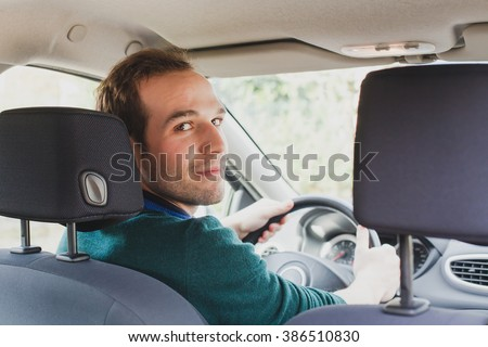 portrait of driver in the car or taxi, young caucasian man