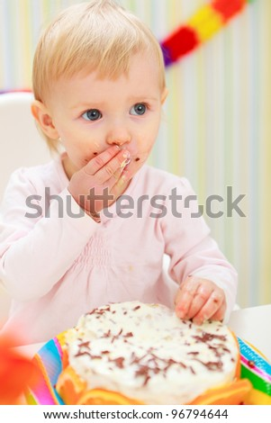 Portrait of eat smeared kid eating cake
