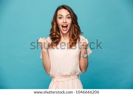 Portrait of ecstatic woman 20s wearing dress screaming and clenching fist like rejoicing victory or triumph isolated over blue background