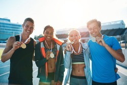 Portrait of ecstatic young runners showing medals. Young men and women looking excited after winner a running race. Team of multiracial athletes in stadium.