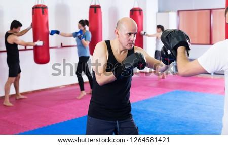 Portrait of elderly active sportsmen competing in boxing gloves