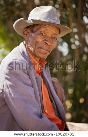 Portrait of elderly  african man with a broken hat and old suit