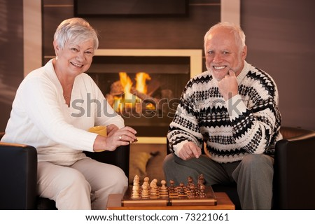 Portrait of elderly couple playing chess at home by fireplace in winter, looking at camera, smiling.?