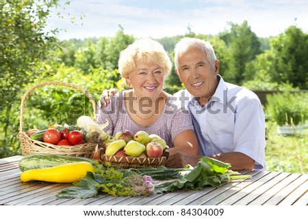 Portrait of elderly couple with fresh vegetables on the table