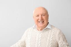 Portrait of elderly man on light background