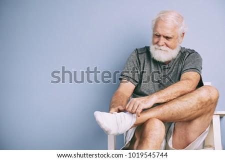 Portrait of elderly man putting on white socks for sports training