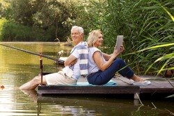 Portrait of elderly people sitting on pier at lakeside. Senior man fishing while his wife using digital tablet and surfing on internet.