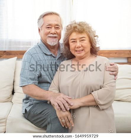 Portrait of elderly senior asian couple happy together at home.Elder man arm hug elder woman shoulder look at camera.