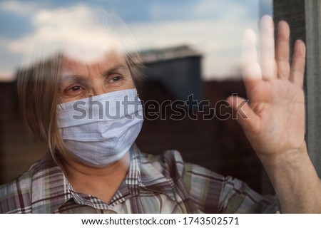 Portrait of elderly senior citizen wearing face mask looking through room window,Coronavirus COVID-19 pandemic outbreak nursing home crisis,high mortality rate and death cases among older population Stockfoto ©