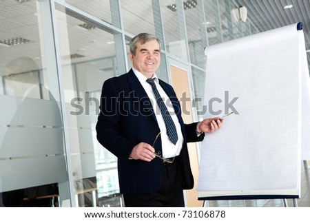 Portrait of elderly teacher pointing at whiteboard in office