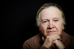 Portrait of elderly woman on dark background. Toned.