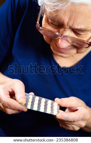 Portrait of elderly woman with pills. Health care