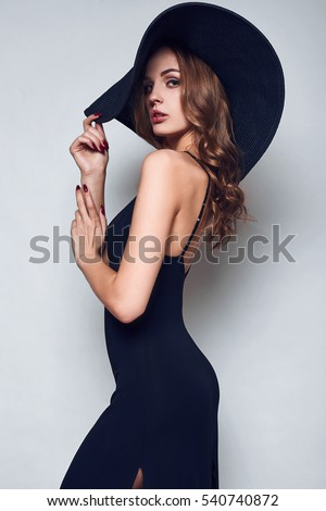 Portrait of elegant beautiful woman in a black dress and wide hat isolated on white background in studio #540740872