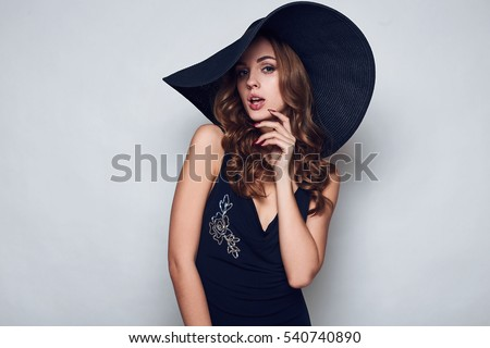 Portrait of elegant beautiful woman in a black dress and wide hat isolated on white background in studio #540740890