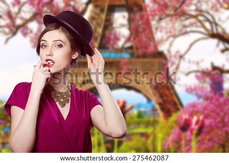 Portrait of elegant beautiful woman in hat over blurred outdoors Paris background at Eiffel tower