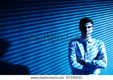 Portrait of elegant businessman looking at camera with blind shades on background
