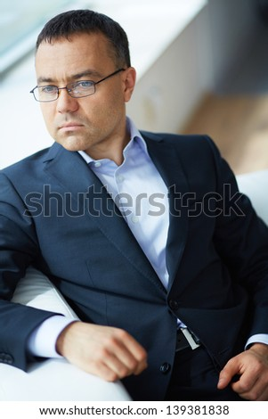 Portrait of elegant businessman sitting in office - stock photo