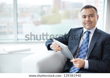 Portrait of elegant businessman with touchpad sitting in office