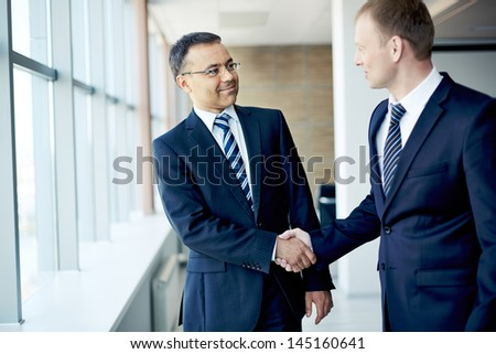 Portrait of elegant businessmen handshaking in conference hall