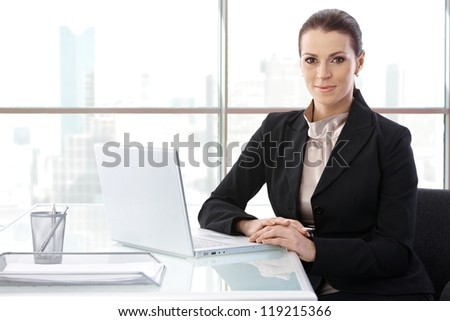 Portrait of elegant businesswoman sitting at desk with laptop computer, smiling at camera, copyspace.