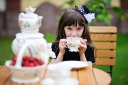 Portrait of elegant child girl in a black dress having a tea party outdoors, focus on the background with girl's face
