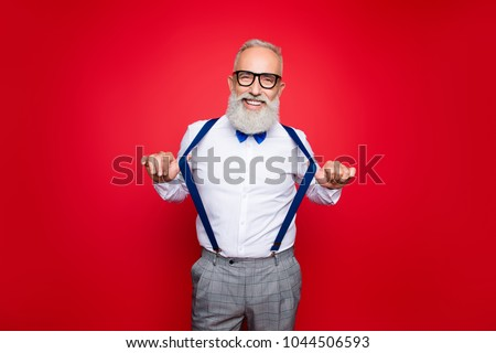 Portrait of elegant, confident, playful macho, old barber, stylist draw off suspenders with thumb fingers, looking at camera with beaming smile, isolated on red background