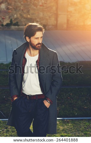 Portrait of elegant fashionable adult man dressed in coat walking on tram-line in urban setting, stylish hipster man walking on the street at sunny evening, flare sunshine