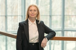 Portrait of elegant mature businesswoman in formalwear looking at camera standing at office