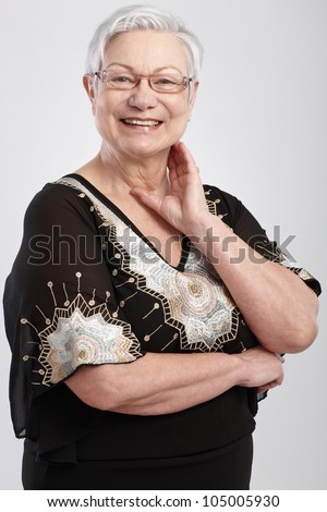 Portrait of elegant old lady smiling, wearing glasses.