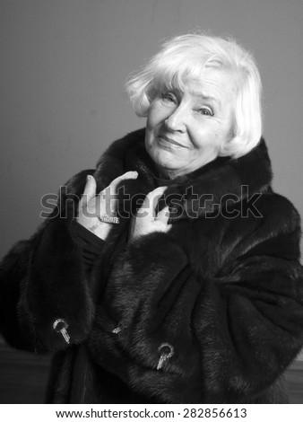 Portrait of elegant senior woman in fur coat