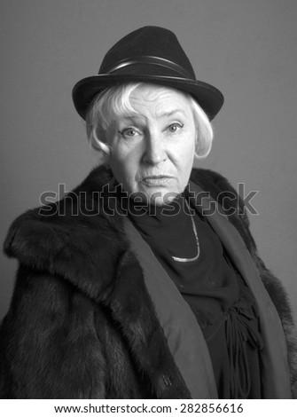 Portrait of elegant senior woman in the hat and fur coat