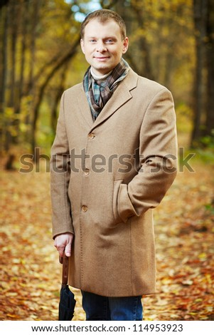 Portrait of elegant young man in coat looking at camera in autumn