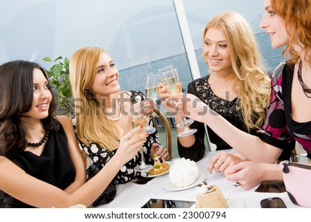Portrait of elegantly ladies with champagne touching their glasses