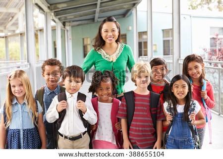 Portrait of elementary school kids and teacher in corridor
