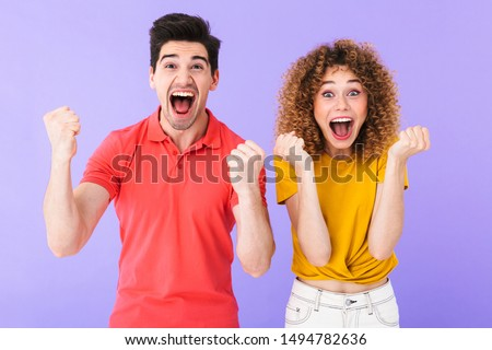 Portrait of emotional caucasian people man and woman in basic clothing screaming and rejoicing together isolated over violet background