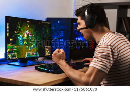 Portrait of emotional gamer guy wearing headset screaming while playing video games on computer