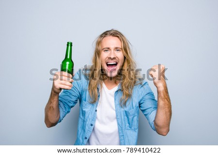 Portrait of emotional, happy, lucky guy screaming celebrating a victory of his favorite team with raise fist, holding bottle of beer, standing over grey background