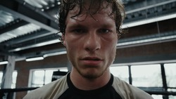 Portrait of emotional kickboxer showing aggression at gym. Closeup aggressive sportsman screaming on ring. Young fighter staring at lens in fitness center.