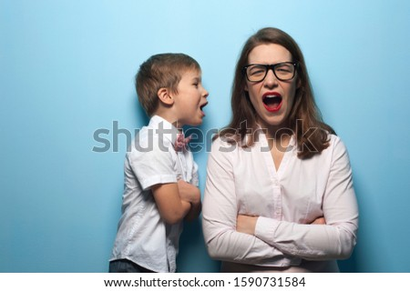 Portrait of emotional mom and baby screaming in her ear on a blue background. Concept of moody and demanding children and tired parents. Advertising space Foto stock ©