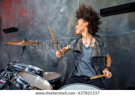 portrait of emotional woman playing drums in studio, drummer rock concept #637821337
