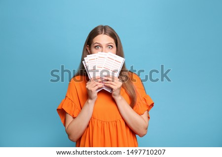 Portrait of emotional young woman with lottery tickets on light blue background