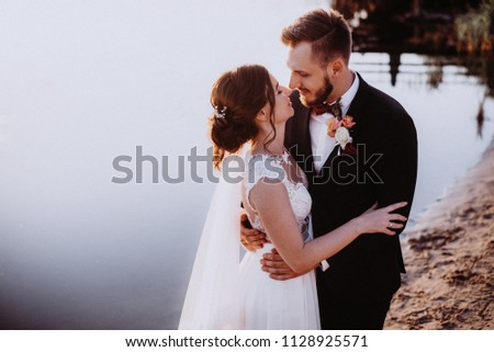 portrait of enamored newlyweds at sunset near lake or river #1128925571