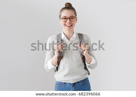 Portrait of energetic teenager girl isolated on gray background pulling forward straps of gray hipster backpack, laughing happily as if anticipating friendly meeting or great leisure time in open air.