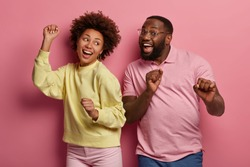 Portrait of energized dark skinned couple dance happily, have inspired joyful face expressions, smile broadly, moves with music, clench fists and raise arms, isolated over rosy pastel background