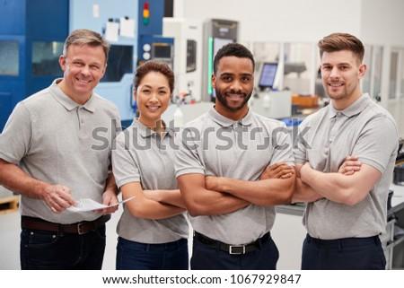 Portrait Of Engineering Team On Factory Floor Of Busy Workshop